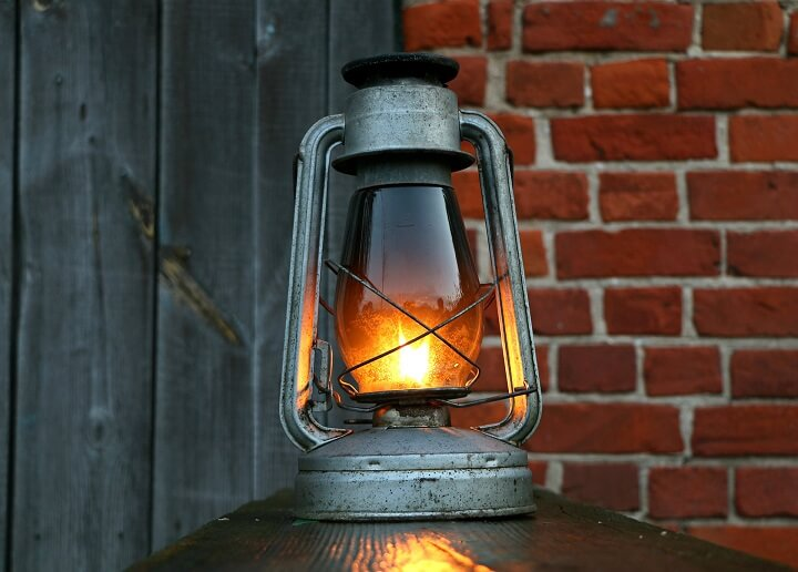 An Old Oil Lamp Sits On A Shelf