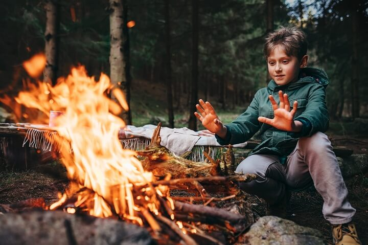 Kid By Campfire