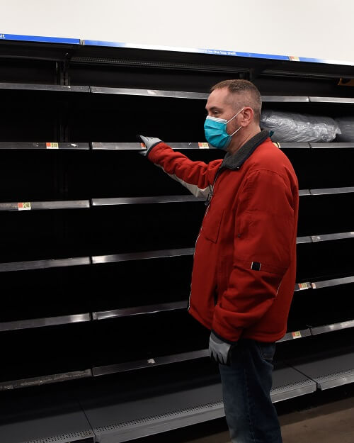 Man in Flu Mask Looking At Empty Shelves