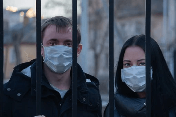 People Behind Bars With Facemasks