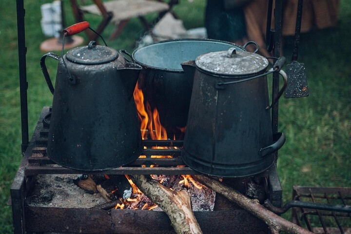 Two Cast Iron Kettles and a Pot over a Campfire