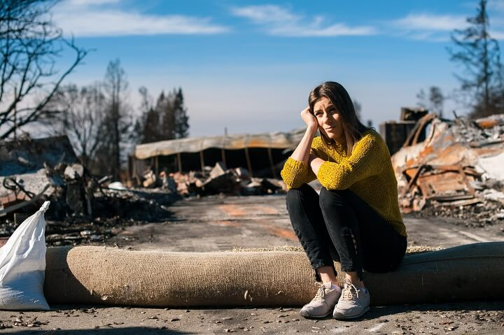 Woman Sitting In Ruins Of Disaster